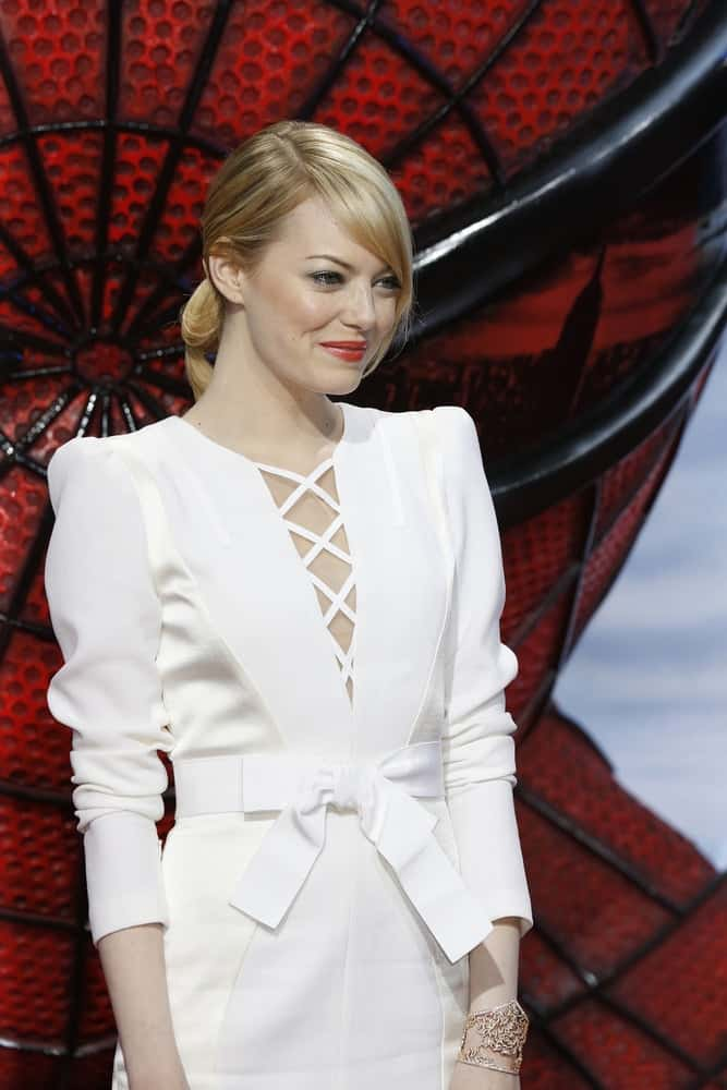 Emma Stone wore a stunning white outfit that totally complemented her highlighted low bun blond hairstyle with loose side-swept bangs at the premiere of