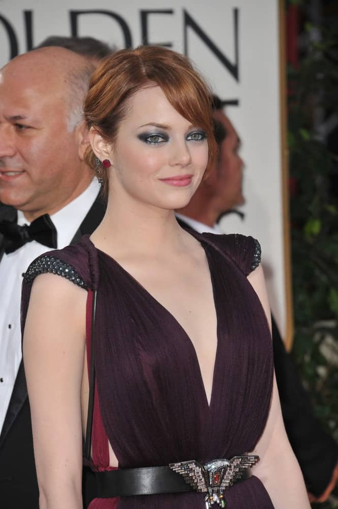 Emma Stone attended the 69th Golden Globe Awards at the Beverly Hilton Hotel on January 15, 2012 in Beverly Hills, CA. She was quite fashionable with her dress, accessories and low bun hairstyle with loose and long side-swept bangs.