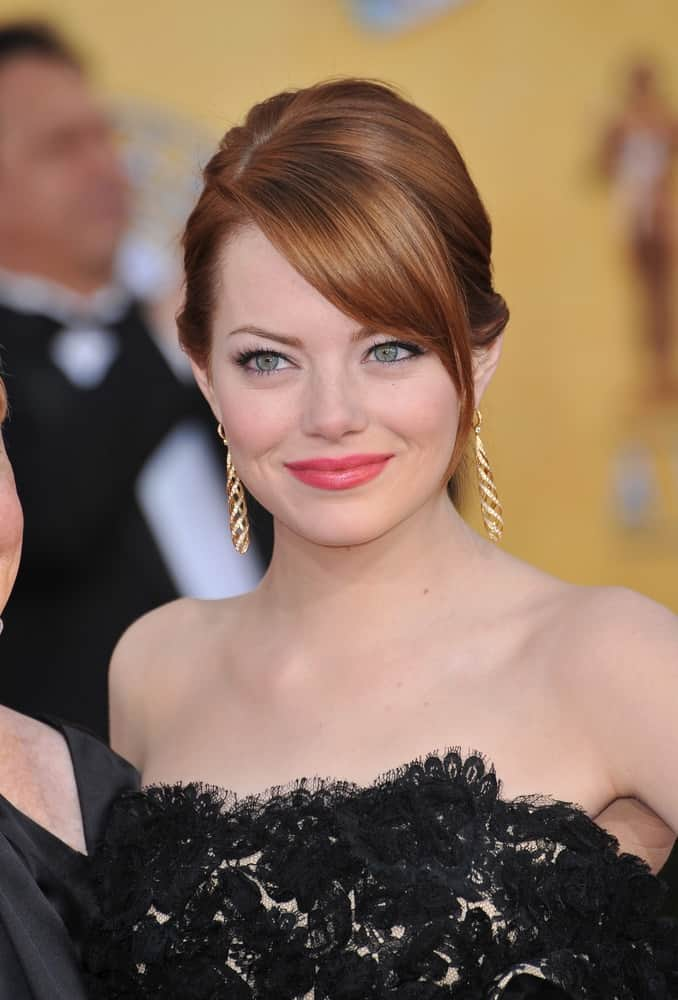 Emma Stone's gorgeous red hair was swept up into a neat bun hairstyle with long side-swept bangs at the 17th Annual Screen Actors Guild Awards at the Shrine Auditorium, Los Angeles on January 29, 2012 in Los Angeles, CA.