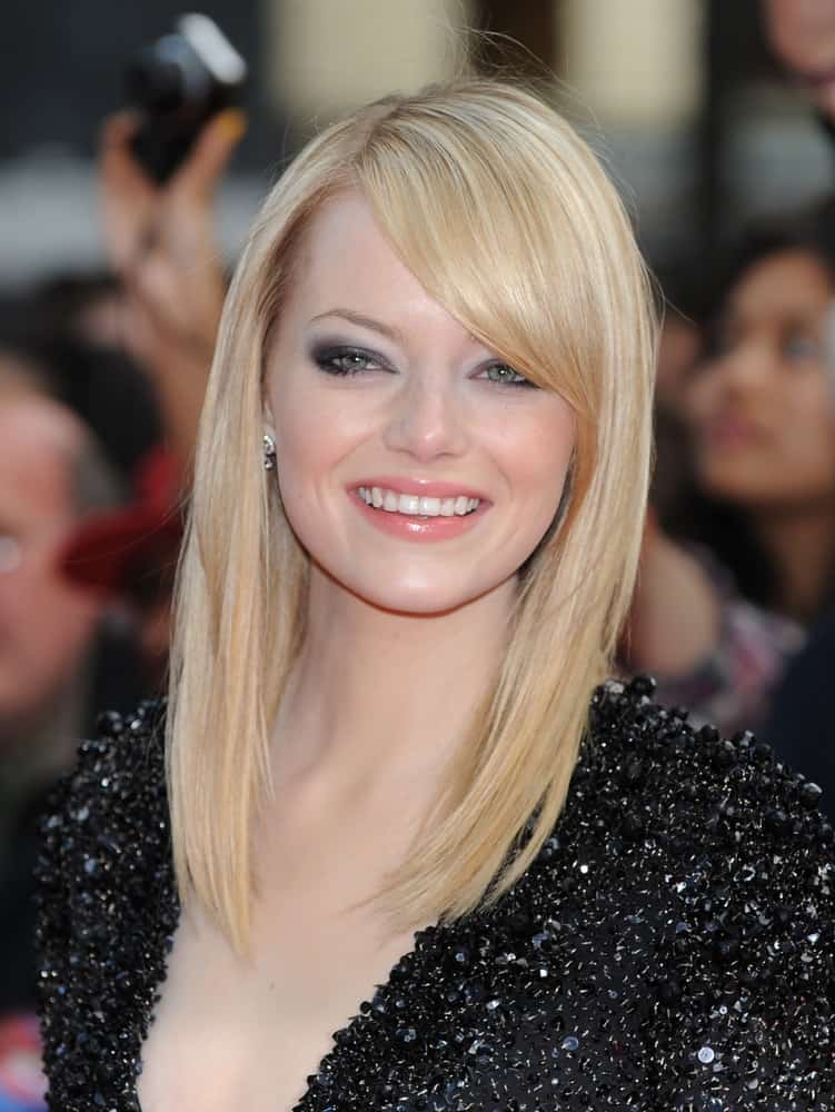 Emma Stone flashed her brilliant smile that went great with her black sequined dress and medium-lenth straight blond hair with side-swept bangs at the Gala Premiere of the film The Amazing Spider-Man held at the Odeon Leicester Square on June 18, 2012.