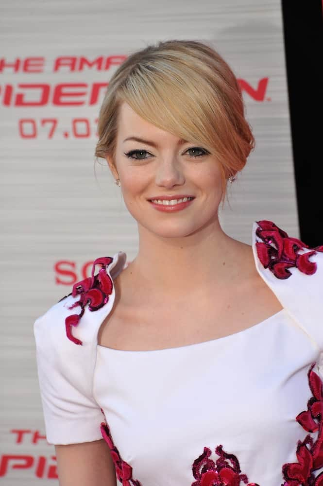 Emma Stone's white dress is incorporated with red floral details and paired with her loose upstyle hair with side-swept bangs at the world premiere of her movie