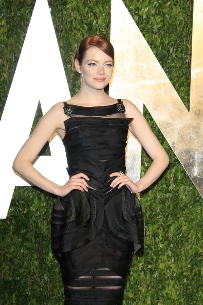 Emma Stone wowed everyone with her detailed black long dress that she paired with her slick and neat red bun hairstyle with side-swept bangs at the Vanity Fair Oscar Party at Sunset Tower on February 26, 2012 in West Hollywood, California.