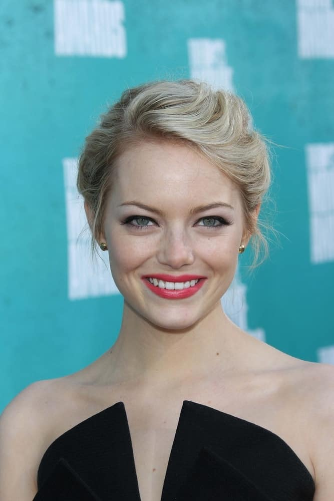 Emma Stone was at the 2012 MTV Movie Awards Arrivals held at the Gibson Amphitheater in Universal City, CA on June 3, 2012. She wore a stunning black dress that paired well with her bold lips and messy upstyle bun hairstyle with a blond hue.