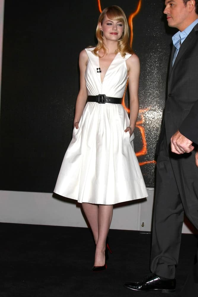 Emma Stone wore an elegant white dress with her shoulder-length sandy blond straight hair with side-swept blunt bangs at the 2013 Academy Award nomination announcements at Samuel Goldwyn Theater on January 10, 2013 in Beverly Hills, CA.