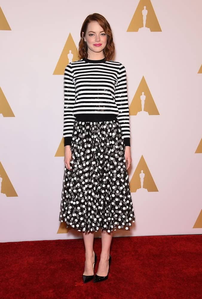 Emma Stone went for a simple yet lovely look with her black and white ensemble outfit that went quite well with her sweet make-up and loose side-swept waves at the Oscar Nominee Reception on February 2, 2015 in Beverly Hills, CA.
