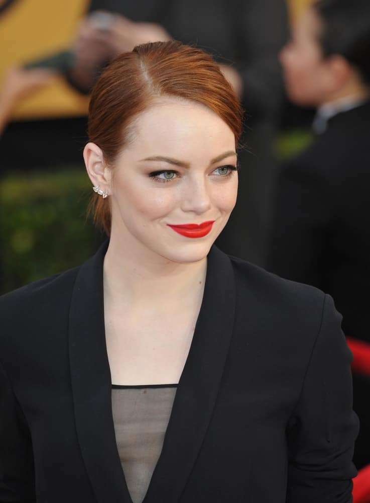 On January 25, 2015, Emma Stone's bold red lips stood out with her confident smile, black outfit and slick low bun hairstyle at the 2015 Screen Actors Guild Awards at the Shrine Auditorium.
