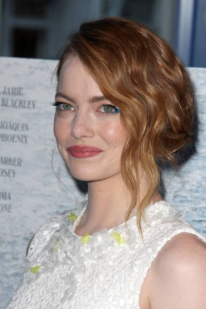 Emma Stone emphasized her gorgeous green eyes with her white floral dress and messy half-up hairstyle that has a slight side-swept finish at the