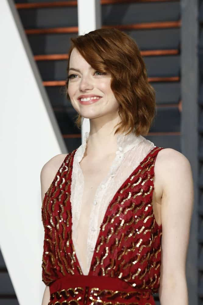 Emma Stone attended the Vanity Fair Oscar Party 2015 at the Wallis Annenberg Center for the Performing Arts on February 22, 2015 in Beverly Hills, CA. She came in a lovely red and gold dress to pair with her short and wavy side-swept hairstyle with a slight tousle.