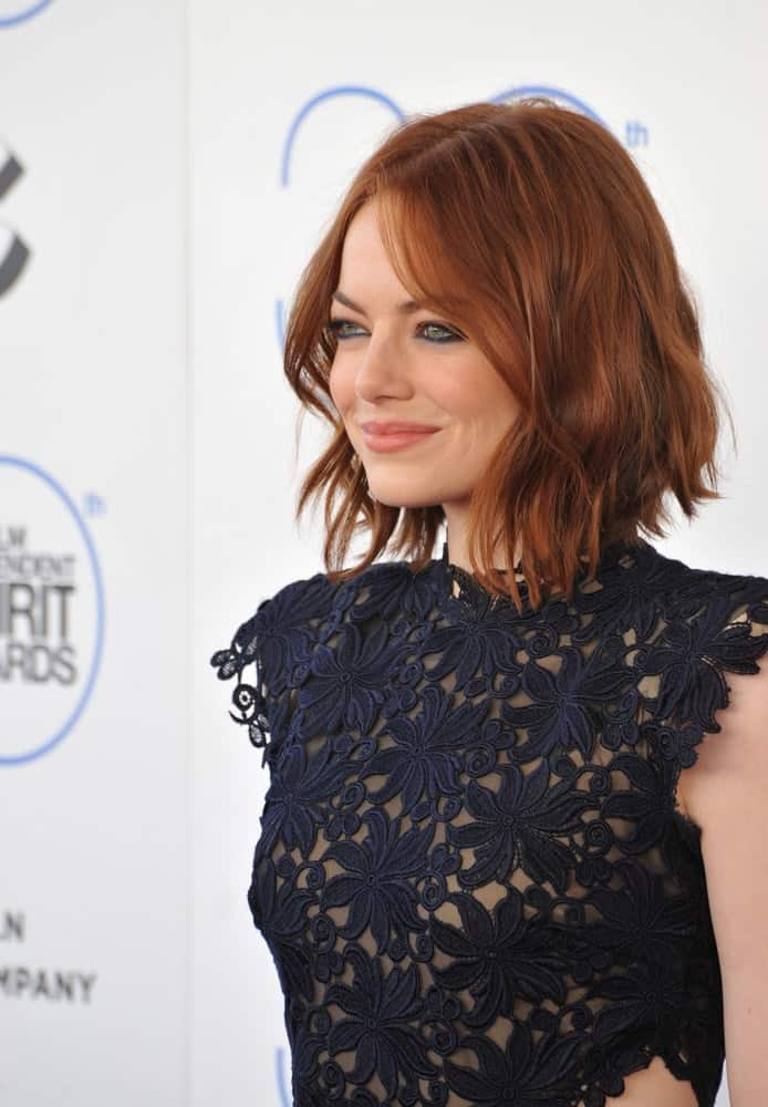 On February 21, 2015, Emma Stone attended the 30th Annual Film Independent Spirit Awards on the beach in Santa Monica. She was quite elegant in her navy blue floral dress with embroidered details that pairs well with her loose and tousled short red hair.