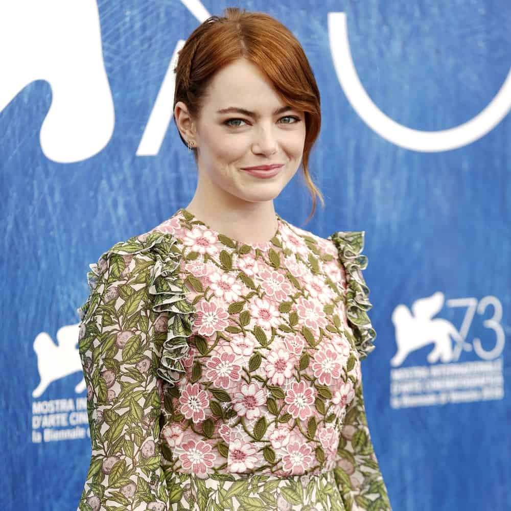 Actress Emma Stone paired her sweet and lovely floral dress with a side-swept bun hairstyle incorporated with long and loose bangs as well as a single braid at the photo-call of 'La La Land' during the 73rd Venice Film Festival on August 31, 2016 in Venice, Italy.