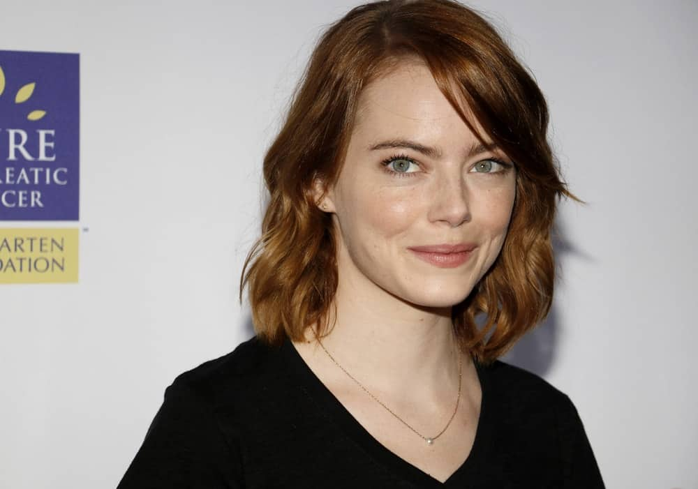 Emma Stone went with a simple black casual shirt and short wavy red hair complemented by long side-swept bangs at the 5th Biennial Stand Up To Cancer held at the Walt Disney Concert Hall in Los Angeles on September 9, 2016.