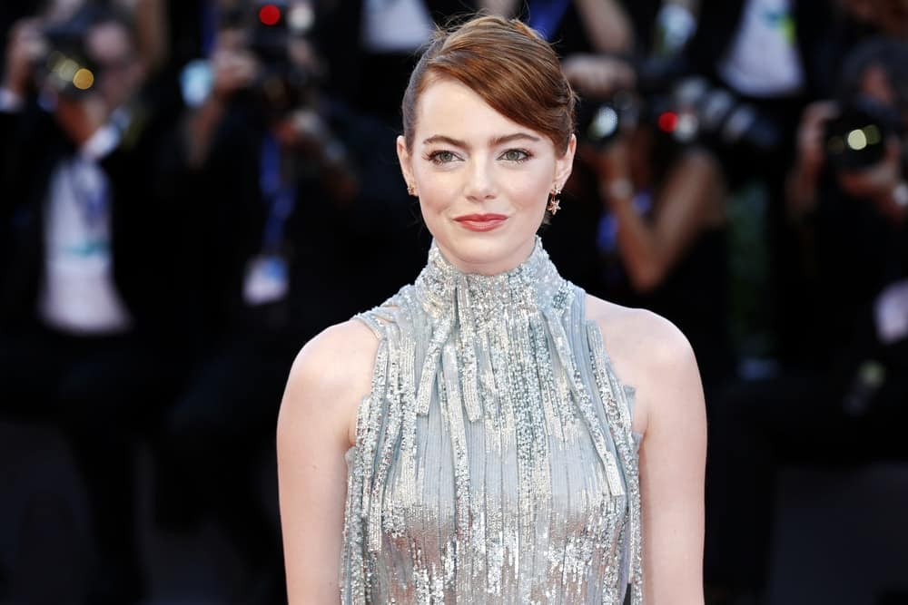 Actress Emma Stone sported an elegant upstyle that has side-swept bangs and a reddish brown hue when she attended the premiere of 'La La Land' during the 73rd Venice Film Festival on August 31, 2016 in Venice, Italy.