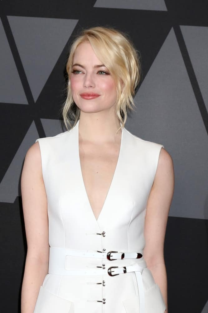 Emma Stone was quite confident with her white outfit that she paired with a bright blond hair styled into a wavy and messy half-up hairstyle with loose bangs at the AMPAS 9th Annual Governors Awards at Dolby Ballroom on November 11, 2017 in Los Angeles, CA.