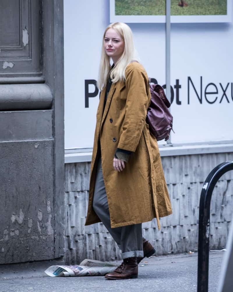 Emma Stone was seen filming 'Maniac' on May 10, 2018 in the streets of New York City. She was walking in casual clothes with a large trench coat, simple make-up and silver blond long straight hair.