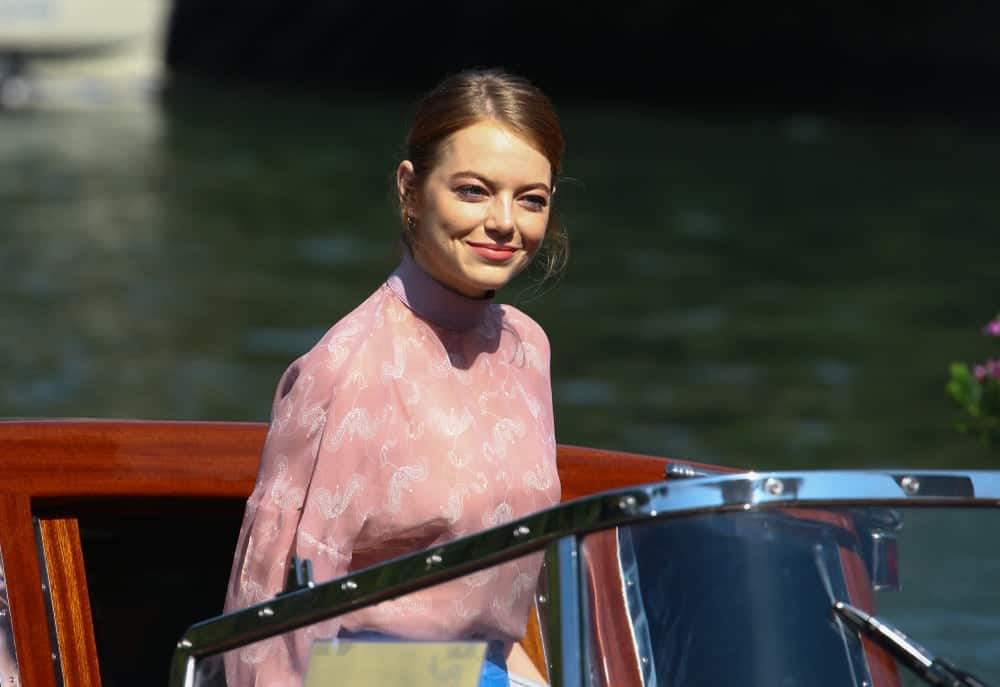 Emma Stone was seen during the 75th Venice Film Festival on August 30, 2018 in Venice, Italy. She was on a boat wearing a casual but lovely pink blouse and her hair was swept up into a slightly messy tight bun.