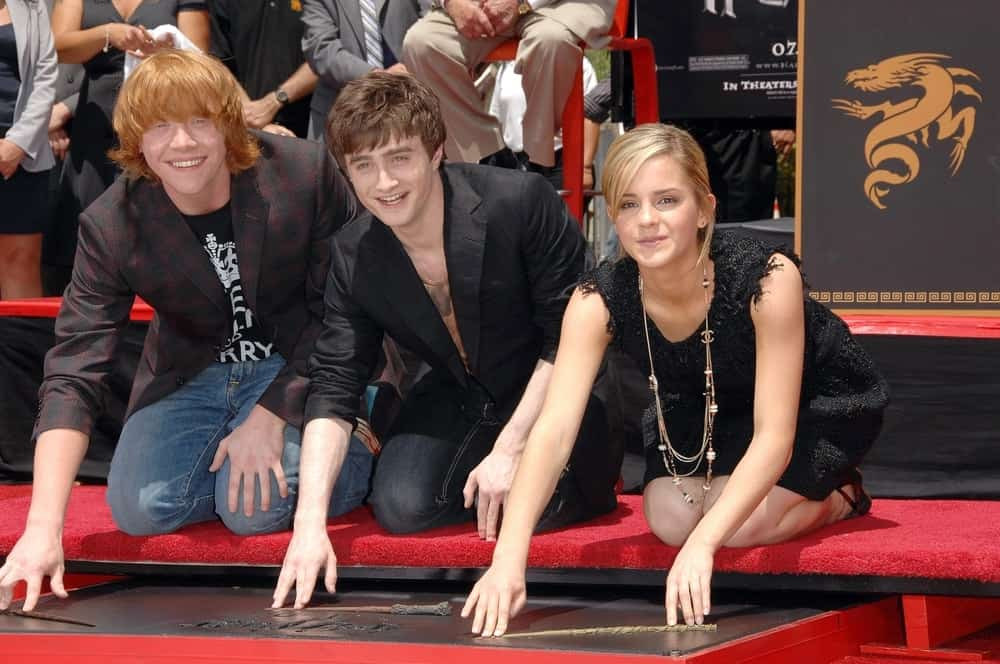 Rupert Grint, Daniel Radcliffe and Emma Watson were at the induction ceremony for Harry Potter Foot-Print and Wand-Print Ceremony in Grauman's Chinese Theatre, Los Angeles on July 09, 2007. Watson had her sandy blond hair in a bun hairstyle with tendrils and side-swept bangs.