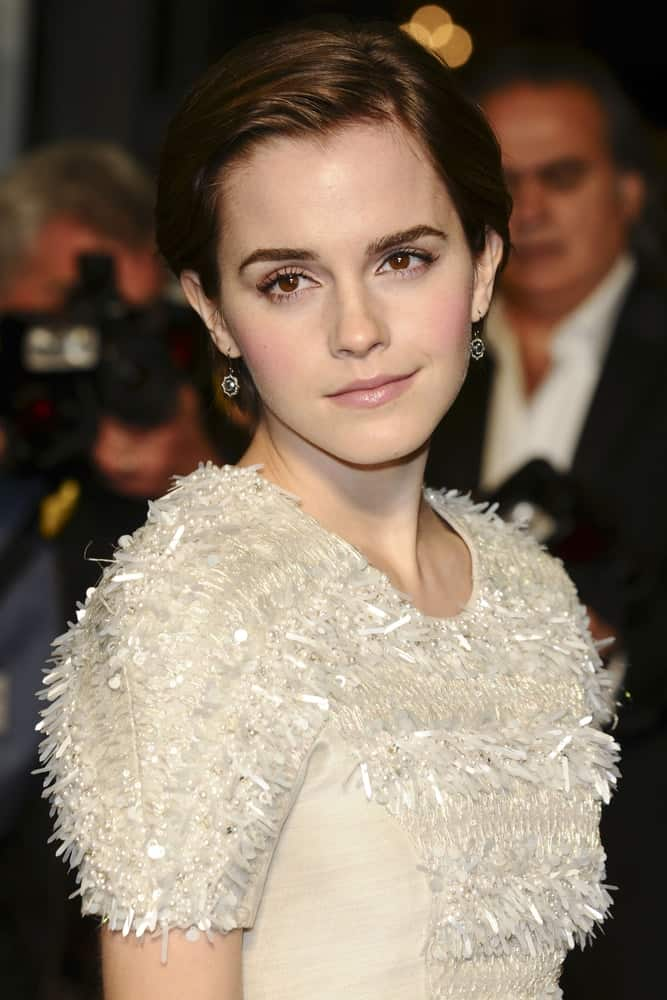 Emma Watson wore a stylish and simple white frilly dress with her elegant side-swept bun hairstyle with a slick finish at the
