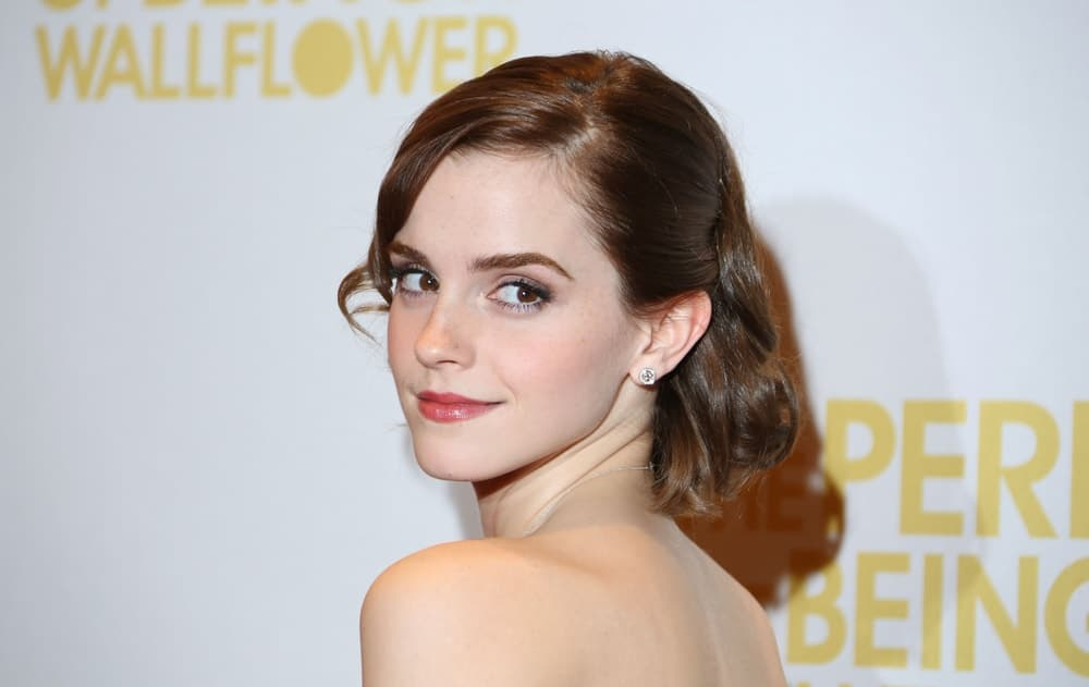 Emma Watson pulled off this elegant and simple short half-up pinned hairstyle with side-swept bangs at