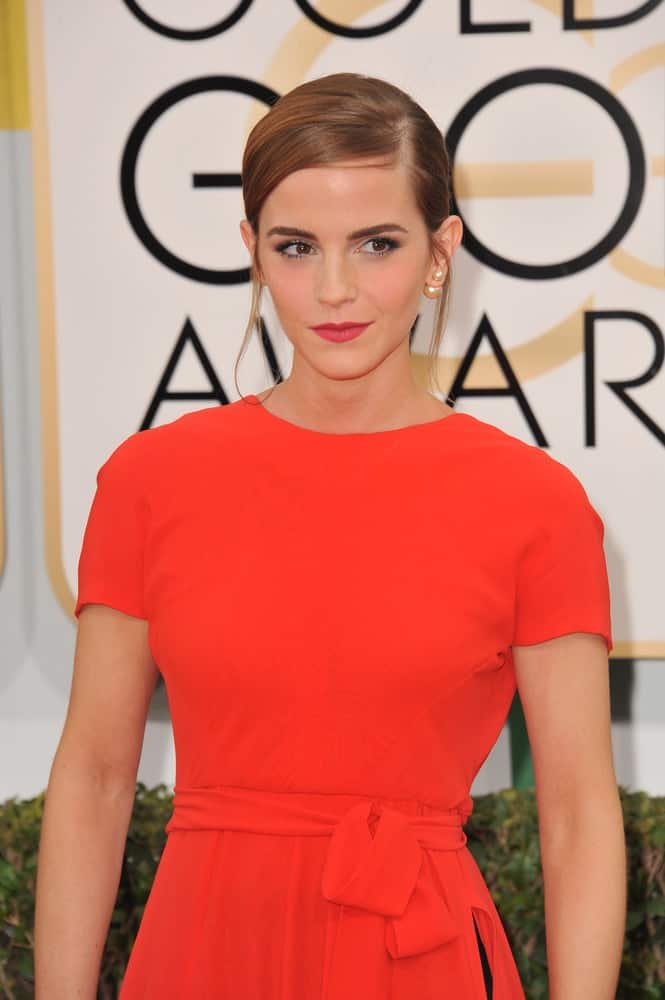On January 12, 2014, Emma Watson attended the 71st Annual Golden Globe Awards at the Beverly Hilton Hotel. She caught everyone's attention with her simple and lovely red orange dress that paired well with the highlights of her slick side-parted hairstyle.