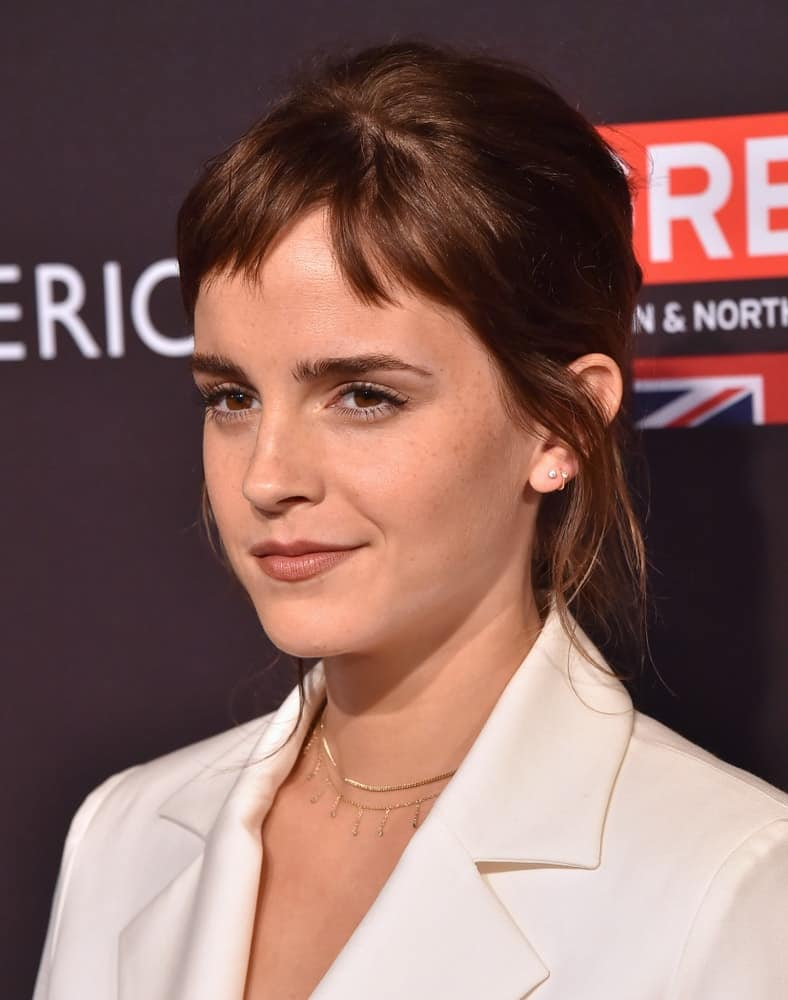 Emma Watson attended the BAFTA Tea Los Angeles on January 06, 2018 in Beverly Hills, CA. SHe was quite classy in her white smart casual outfit to pair with her messy bun upstyle with short bangs and tendrils.