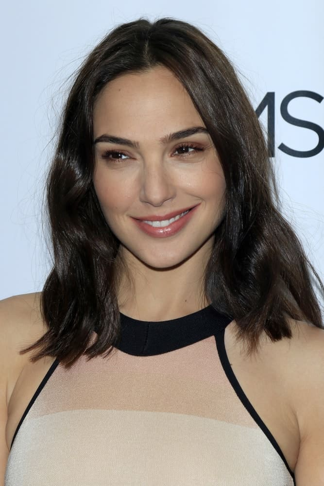 Gal Gadot was at the The Moms Present a Screening of 'Keeping Up With the Joneses' at London Hotel on October 20, 2016 in West Hollywood, CA. She came in a simple beige dress that she paired with simple makeup and shoulder-length loose tousled hair with subtle layers.