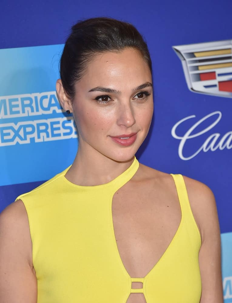 Gal Gadot was at the 2018 Palm Springs International Film Festival Awards Gala on January 2, 2018 in Palm Springs, CA. She wore an elegant bright yellow gown with her slick bun hairstyle and simple makeup.