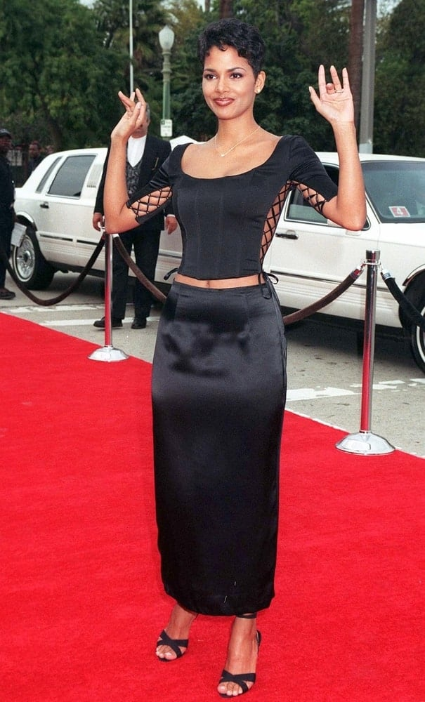 Young actress Halle Berry wore a black two-piece dress, black heels and a curly pixie hairstyle with a slight side-swept look at the Blockbuster Entertainment Awards on March 11, 1997.