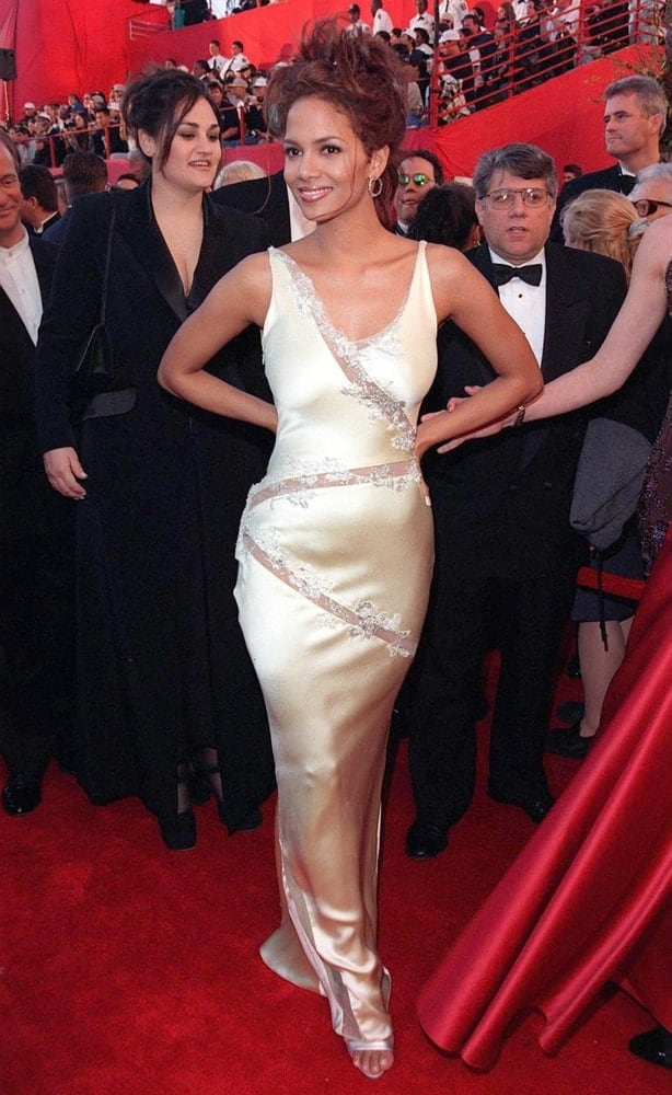 Actress Halle Berry was at the 70th Academy Awards on March 23, 1998. She came wearing an elegant pearly long dress that she topped with a reddish messy tousled upstyle hair with loose tendrils.