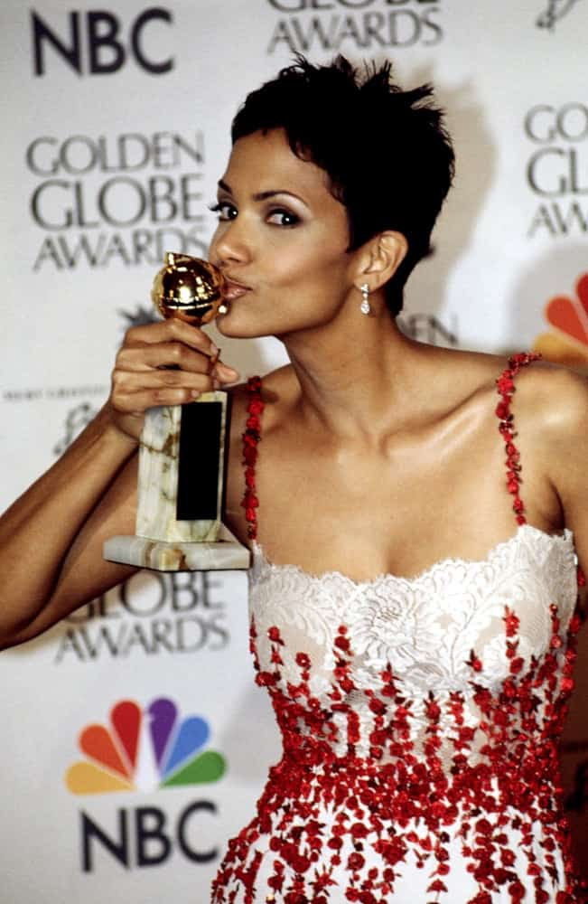 Halle Berry giving a smooch to her Golden Globe Award trophy in January of 2000. She wore a lovely white and red dress to the event that she paired with a spiky pixie hairstyle.