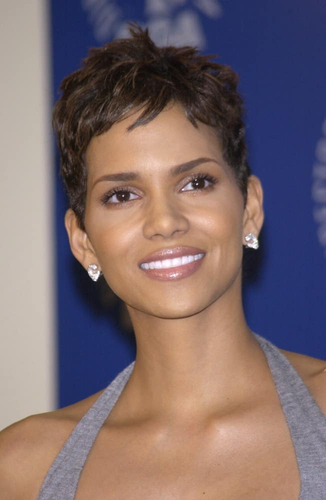On March 9, 2002, Actress Halle Berry was at the 54th Annual Directors Guild Awards in Beverly Hills. She came wearing a simple gray outfit to pair with her tousled pixie hairstyle with subtle highlights.