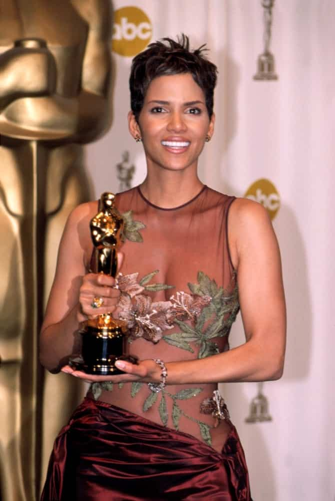 Halle Berry was brimming with pride as she held her Oscar trophy at the Academy Awards in Los Angeles, CA on March 24, 2002. She wore a stylish and sexy sheer dress with her highlighted and spiked pixie hairstyle.