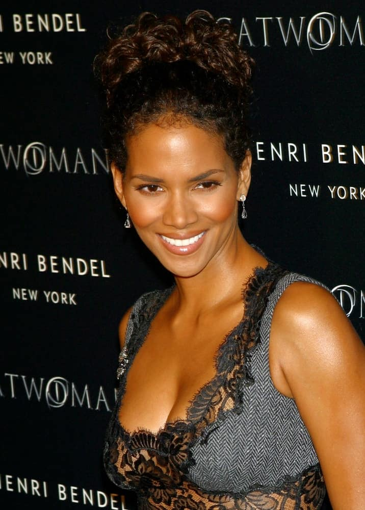 Halle Berry flashed her beautiful smile at the Henri Bendel and Warner Brothers PURR-FECT CATWOMAN event in New York on July 21, 2004. She wore a sexy embroidered dress to match her curly bun upstyle.