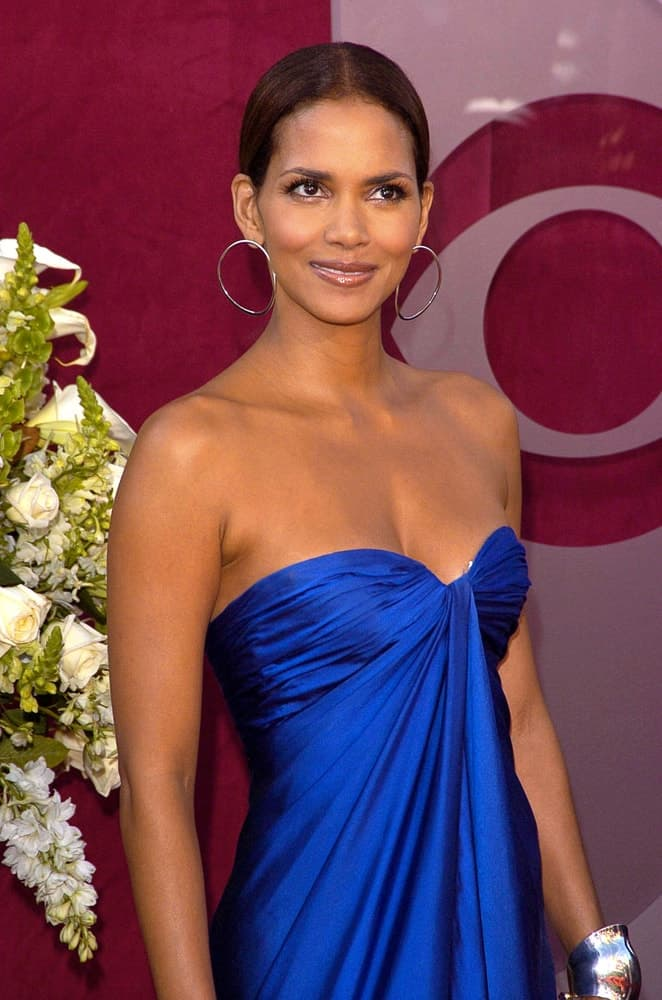 Halle Berry was at the 57th Annual Primetime Emmy Awards held at The Shrine Auditorium in Los Angeles, CA on September 18, 2005. She wore a blue vintage dress that worked quite well with her slick bun hairstyle and hoop earrings.