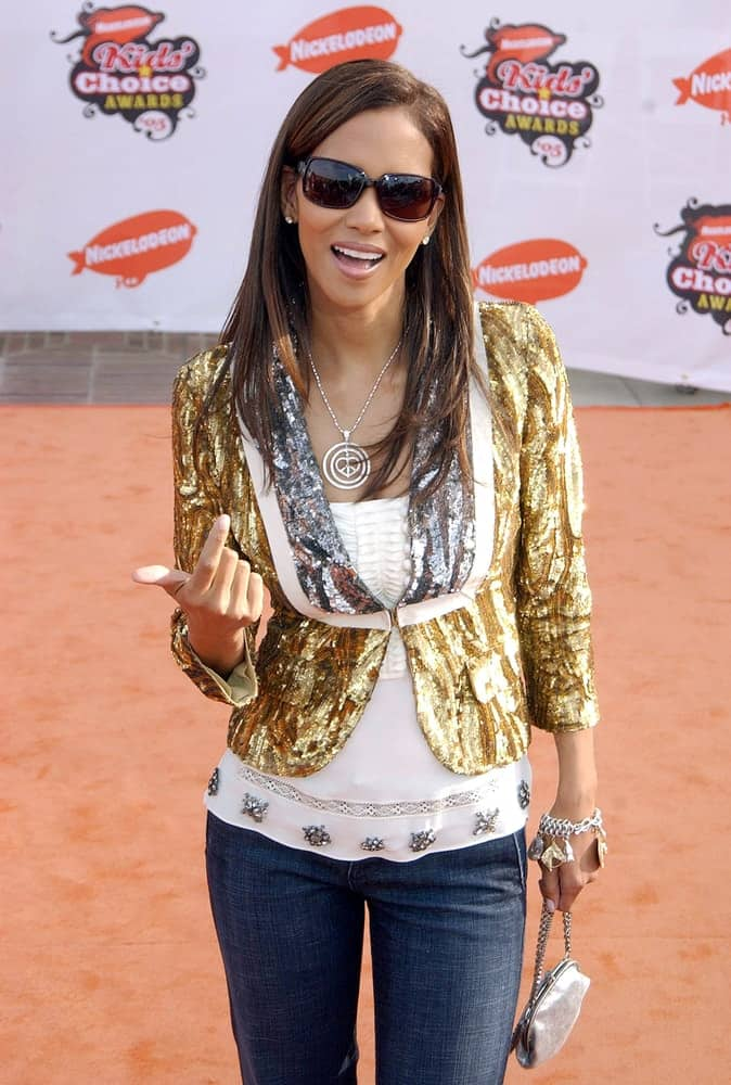 Halle Berry kept it casual and simple with a blouse and jeans outfit at the Nickelodeon Kid's Choice Awards in UCLA Pauley Pavilion, Los Angeles, CA on April 02, 2005. She paired this with a long and straight highlighted hairstyle with side-swept bangs.