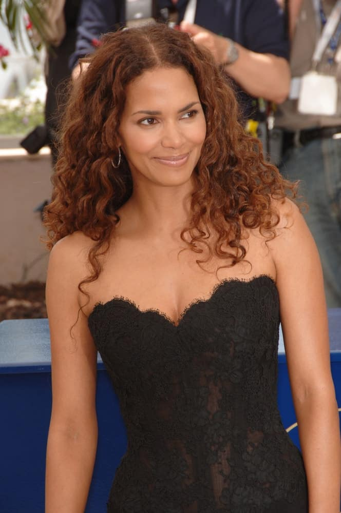 Actress Halle Berry was lovely in her embroidered black dress and loose tousled curly hair that has a reddish hue at the photocall for