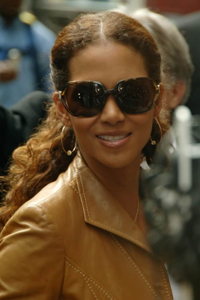 Halle Berry paired her casual tan leather jacket with a pair of cool sunglasses and long, curly ponytail hairstyle at The Late Show with David Letterman held at The Ed Sullivan Theater in New York, NY on May 25, 2006.