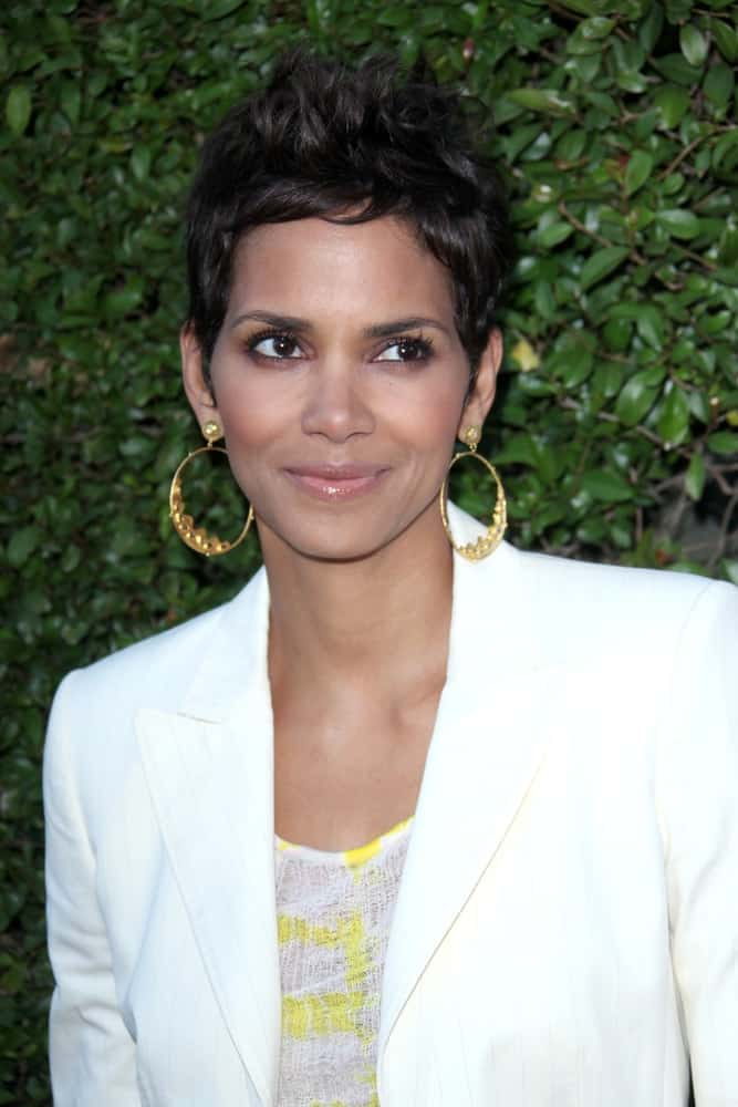 Halle Berry paired her bright white smart casual outfit with golden hoop earrings and a tousled spiked pixie hairstyle at the Opening Night of the Beauty Culture Exhibit at The Annenberg Space For Photography on May 19, 2011 in Century City, CA.