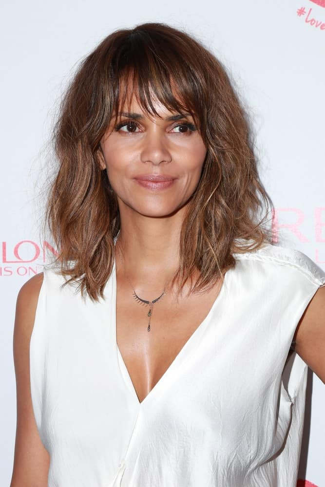 Halle Berry was at the Revlon Celebrates Achievements In Cancer Research at the Four Seasons Hotel on June 3, 2015 in Los Angeles, CA. She wore a simple yet lovely white outfit to go with her shoulder-length tousled hairstyle with highlights and bangs.
