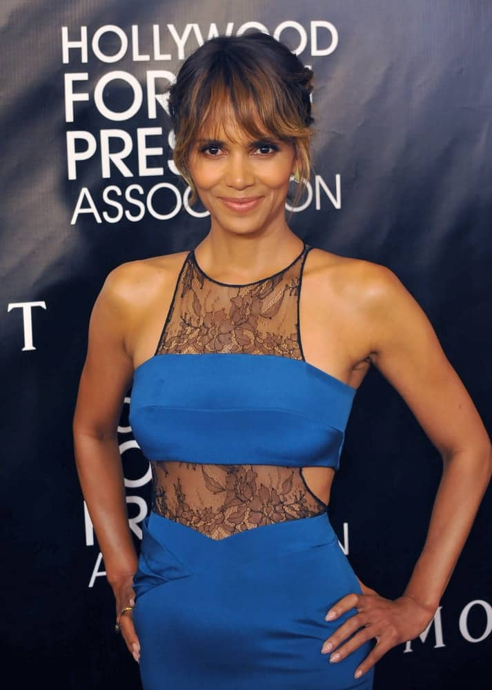 On August 13, 2015, Halle Berry wore a sexy blue dress with her upstyle bun that has loose highlighted wispy bangs at the Hollywood Foreign Press Association's Grants Banquet at the Beverly Wilshire Hotel.