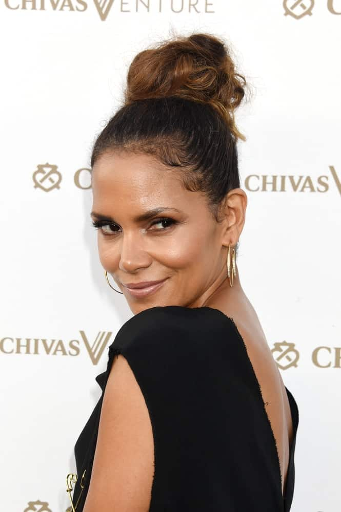 Halle Berry emphasized her sexy neckline with a black dress that she paired with her top knot high bun hairstyle when she arrived at