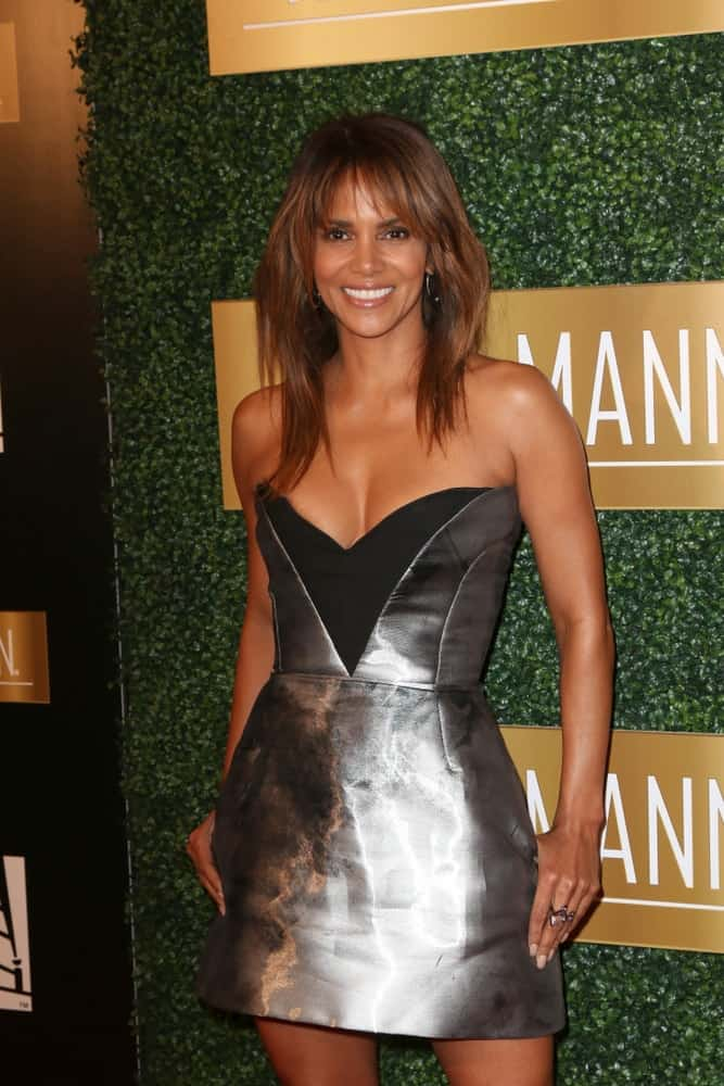 Halle Berry paired her fashionable and stylish silver short dress with a loose and tousled highlighted medium-length hair with wispy bangs at the 6th Annual ICON MANN Pre-Oscar Dinner at Beverly Wilshire Hotel on February 27, 2018 in Beverly Hills, CA.