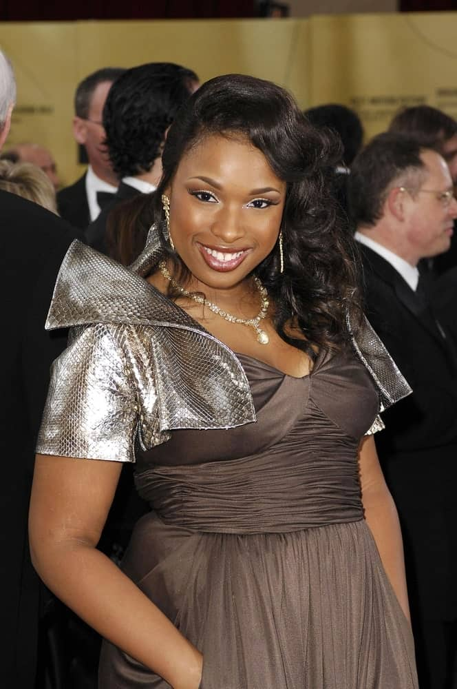 Jennifer Hudson was at the 79th Annual Academy Awards at The Kodak Theatre in Los Angeles, CA on February 25, 2007. She wore a fashionable dress with her long raven curly side-swept hairstyle.