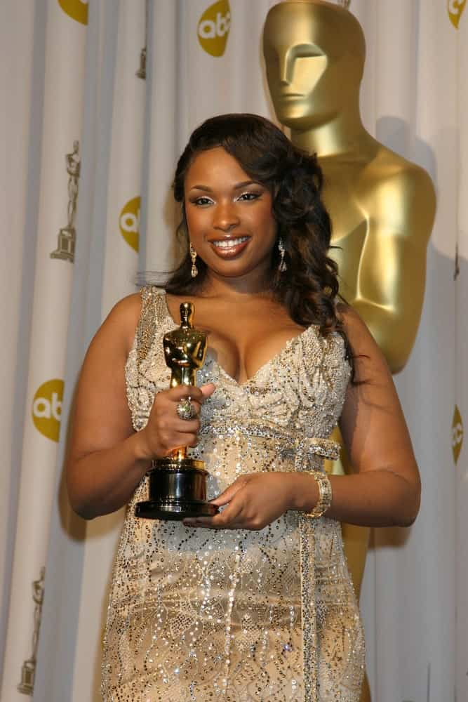 Jennifer Hudson attended the 79th Annual Academy Awards at the Kodak Theater Hollywood & Highland in Hollywood, CA on February 25, 2007. She paired her elegant golden dress with a side-swept loose and tousled curly hairstyle.