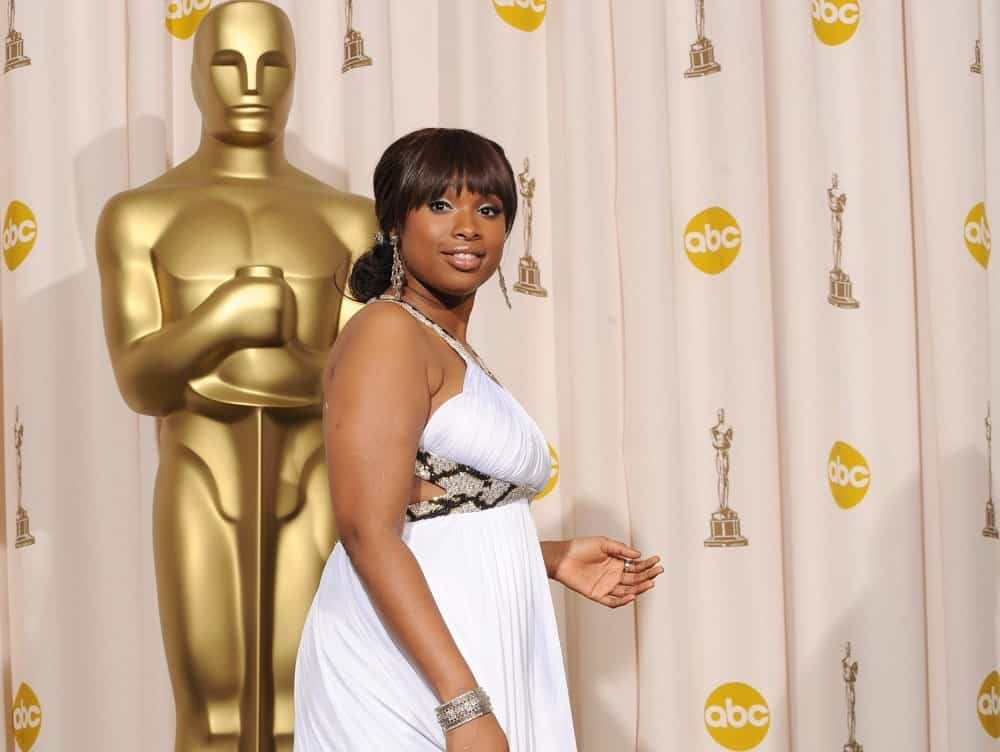 Jennifer Hudson was at the 80th Annual Academy Awards at the Kodak Theatre, Hollywood on February 24, 2008. She paired her lovely white dress with a low bun hairstyle that has blunt bangs.