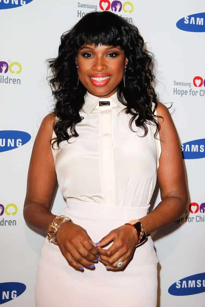 Singer Jennifer Hudson attended Samsung's annual Hope for Children gala at the American Museum of Natural History on June 4, 2012 in New York City. She wore a lovely white dress with her long and curly tousled raven hairstyle with bangs.