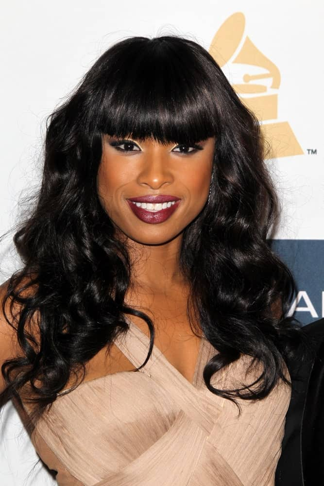 Jennifer Hudson was at the Clive Davis 2013 Pre-GRAMMY Gala at the Beverly Hilton Hotel on February 9, 2013 in Beverly Hills, CA. She wore a sexy beige dress with her long, curly and tousled hairstyle that has blunt bangs.