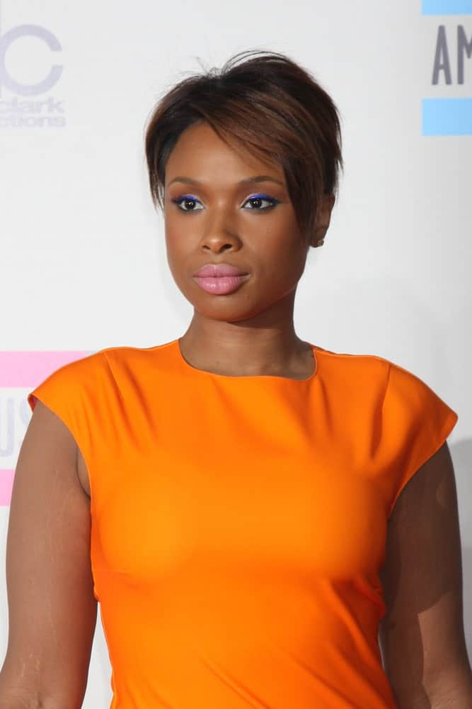 Jennifer Hudson attended the 2013 American Music Awards Arrivals at Nokia Theater on November 24, 2013 in Los Angeles, CA. She was charming in an orange dress that she paired with her side-parted and highlighted pixie hairstyle.