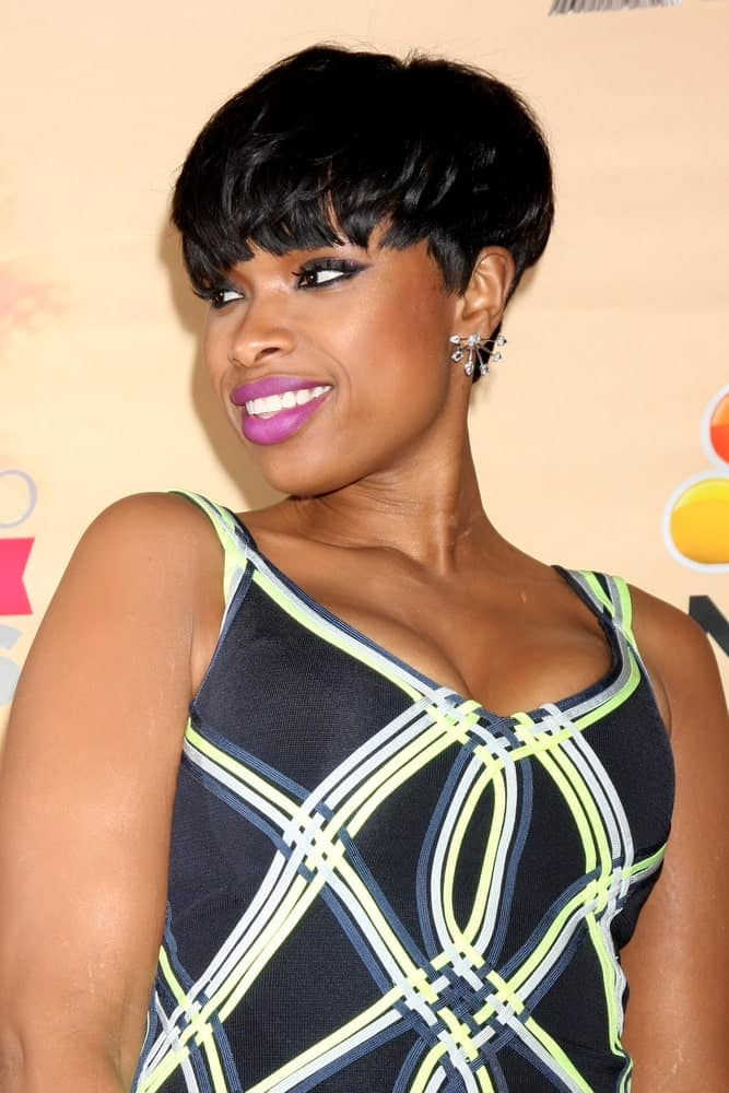 Jennifer Hudson was at the 2015 iHeartRadio Music Awards Press Room at the Shrine Auditorium on March 29, 2015 in Los Angeles, CA. She wore a black patterned dress with her shiny raven bowl cut pixie hairstyle.