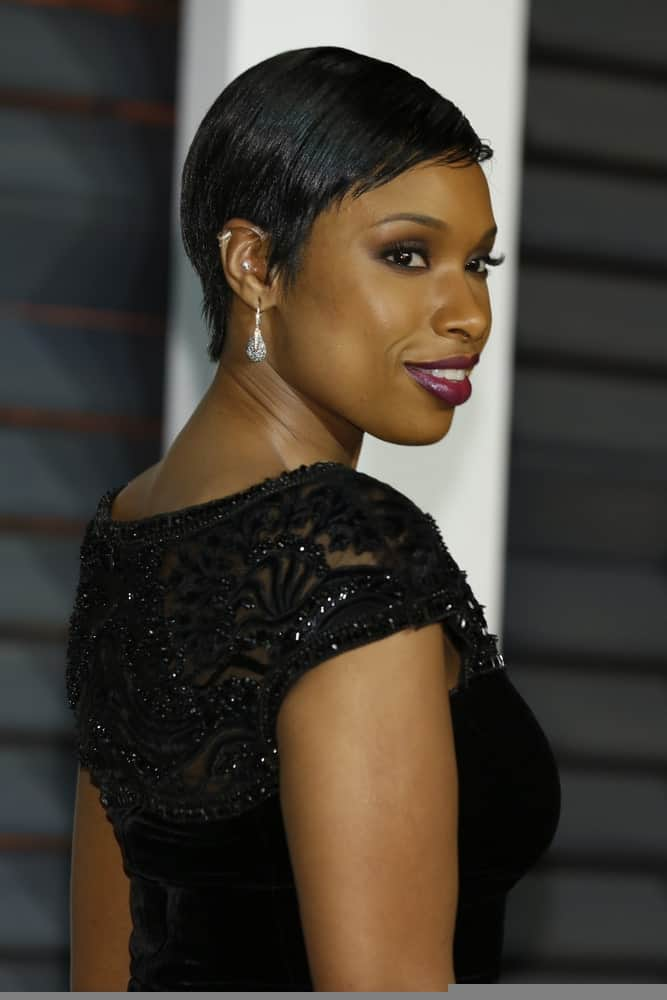 Jennifer Hudson attended the Vanity Fair Oscar Party 2015 at the Wallis Annenberg Center for the Performing Arts on February 22, 2015 in Beverly Hills, CA. She wore a black dress that she topped iwth a side-parted and side-swept slick pixie hairstyle.