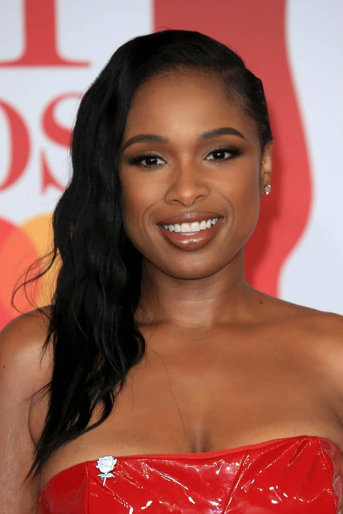On February 21, 2018, Jennifer Hudson attended The BRIT Awards 2018 at the O2 Arena in London, UK. She wore a sexy red leather strapless dress to pair with her long, wavy side-swept raven hairstyle.
